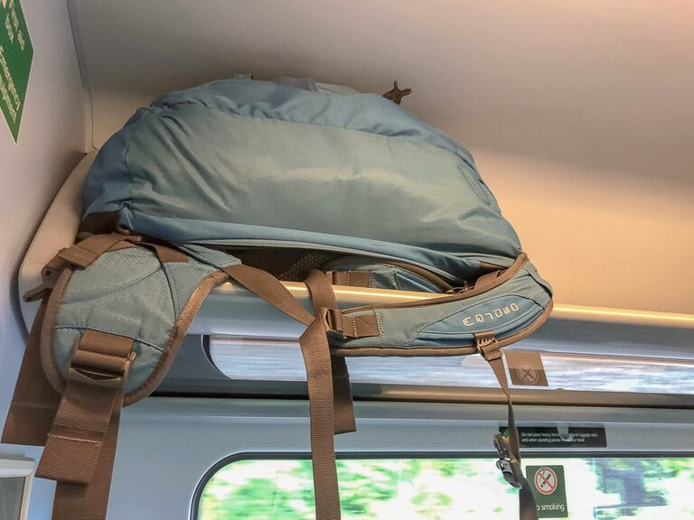 Blue Osprey backpack on an overhead train rack easily fitting