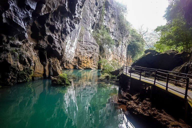 inside Phong Nha dark cave looking back out with boardwalk