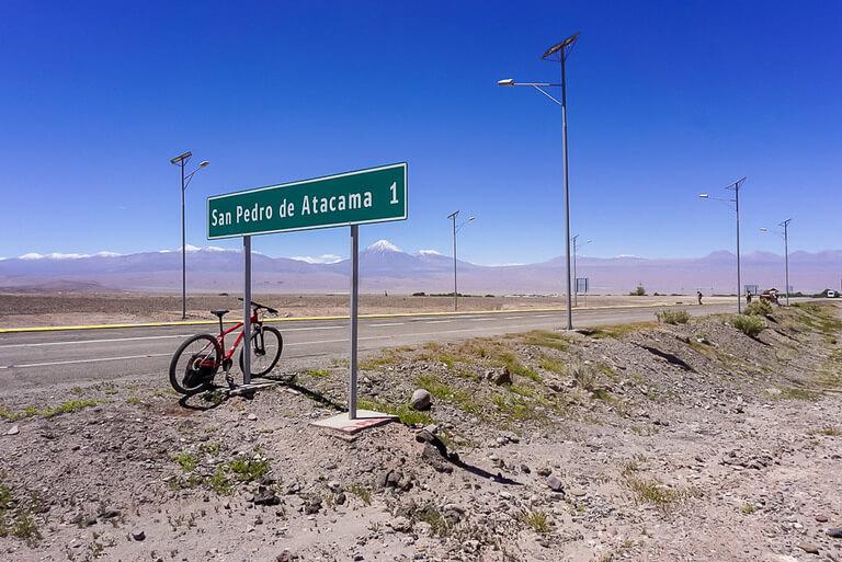 san pedro de atacama 1 kilometer sign with our bike propped up