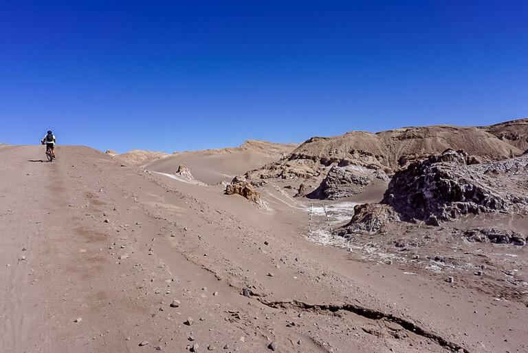 Mark riding bike uphill on dirt path in valle de la luna