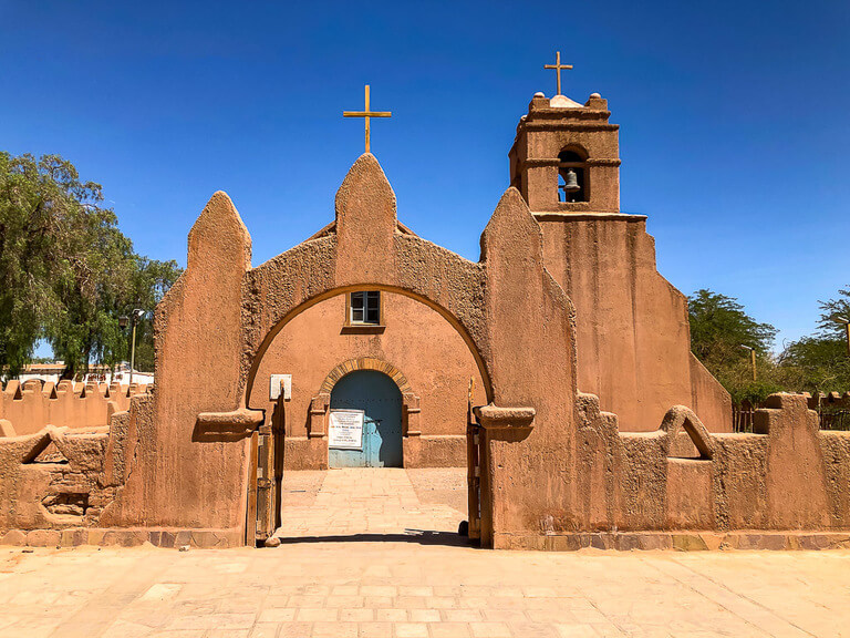 orange clay church with brilliant blue sky in San Pedro de atacama town