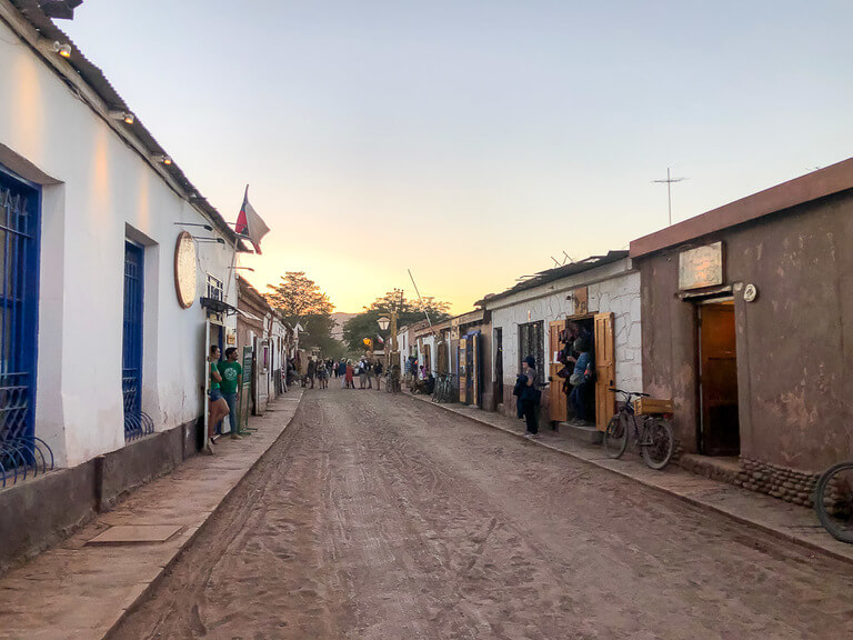 dirt road and shops with owners on street sunset San Pedro town