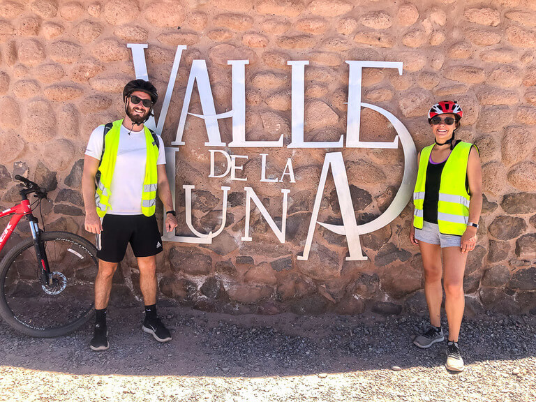mark and kristen with mountain bike in front of valle de la luna entrance sign