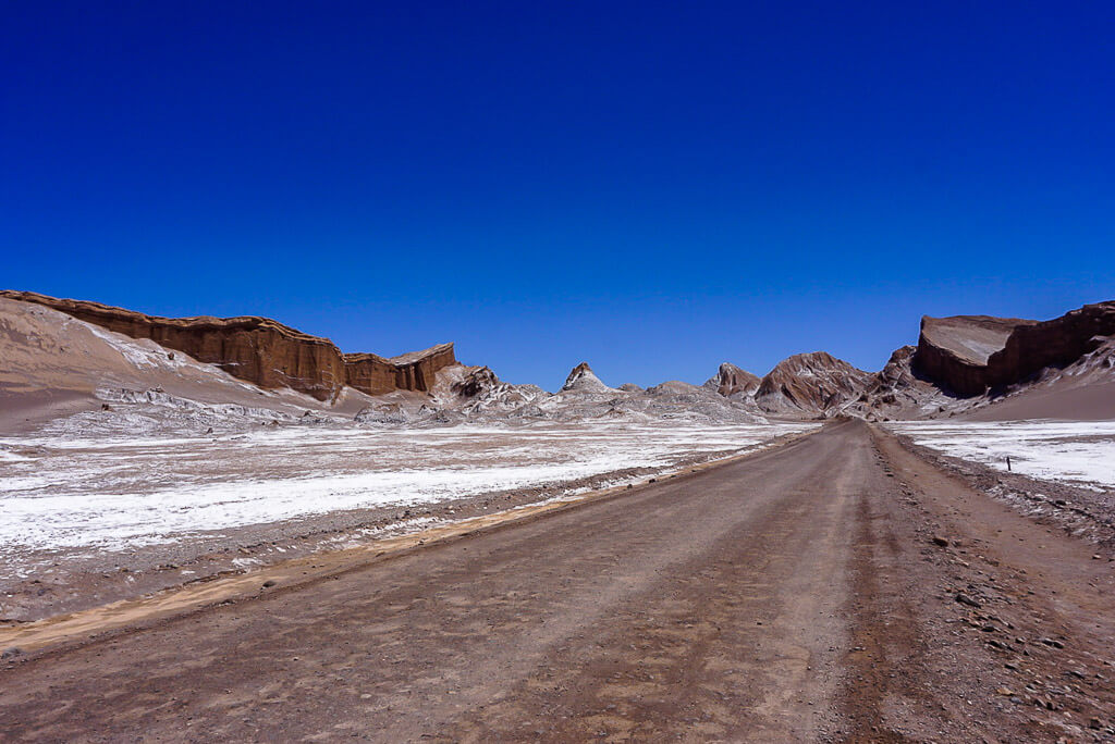 road running through amphitheater in valle de la luna