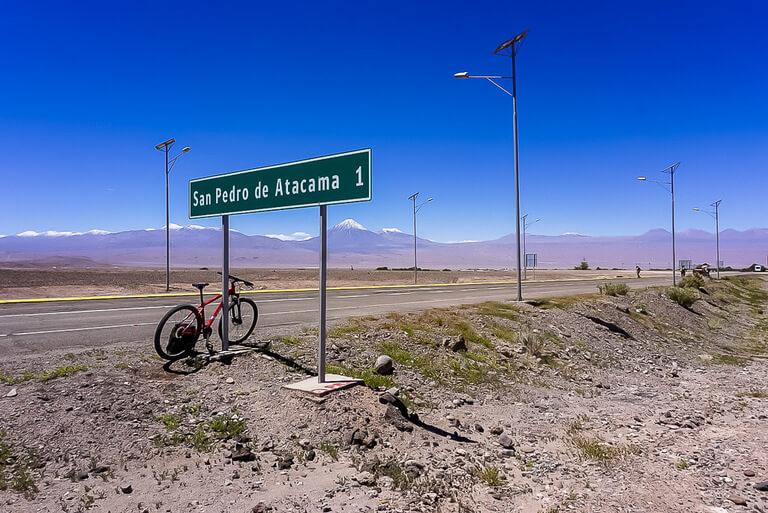 mountain bike propped up against road sign near valle de la luna