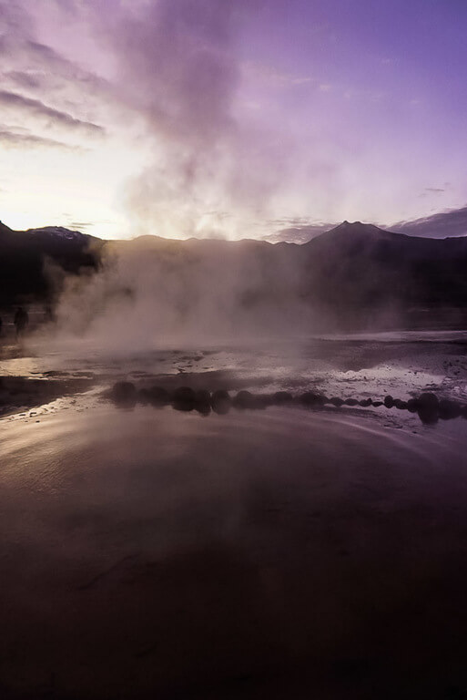 Still water reflecting early morning purple color through steam at el Tatio geysers