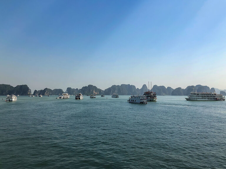 loads of cheap Halong Bay cruise boats sailing into limestone rocks
