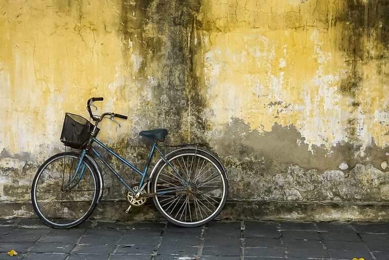 Blue bicycle leaning against yellow wall in Hoi An Vietnam