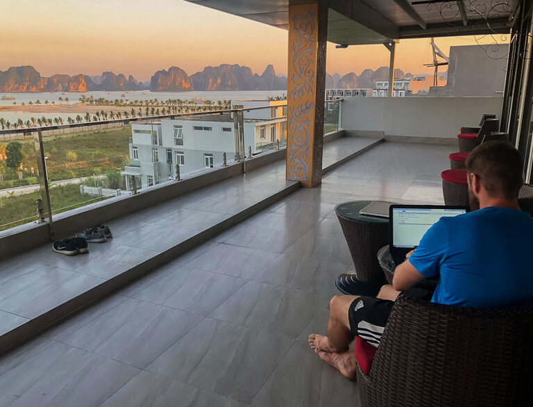 mark working on laptop on balcony with amazing view of Halong Bay at dusk