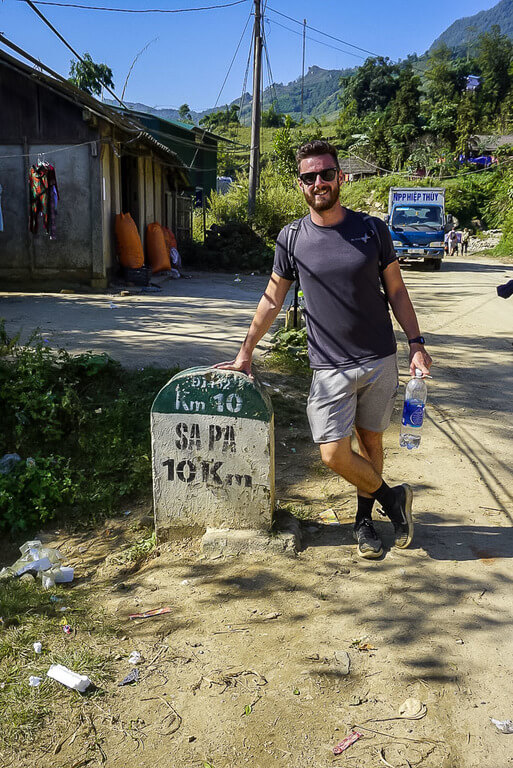 Mark stood next to 10km sapa stone sign in sunshine
