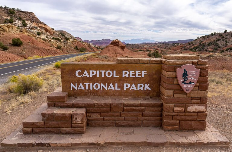 Capitol Reef entrance sign made of bricks with road to left