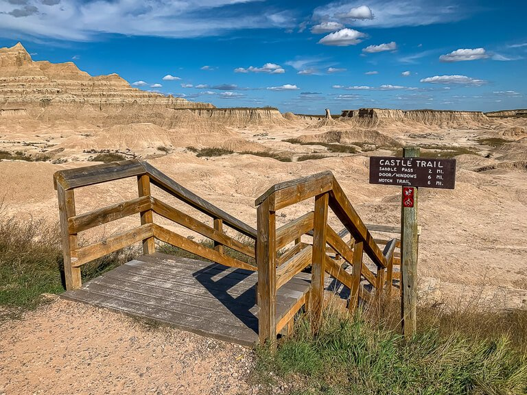 Castle trailhead with wooden staircase and rocks in background
