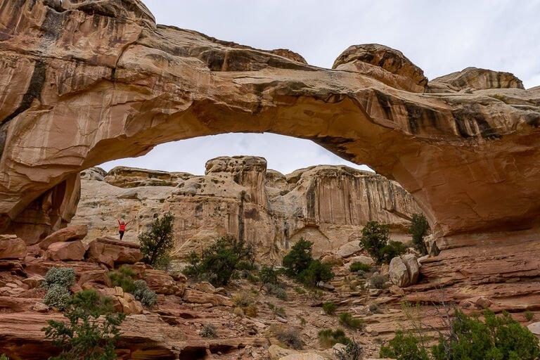 Kristen stood underneath Hickman Bridge natural rock formation in Utah