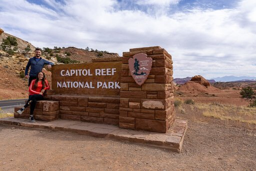 Mark and kristen leaning against Capitol Reef entrance sign Utah