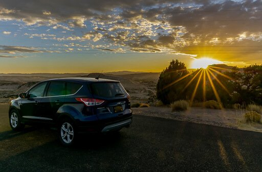 our car at sunset with sunburst near Capitol Reef highway 12