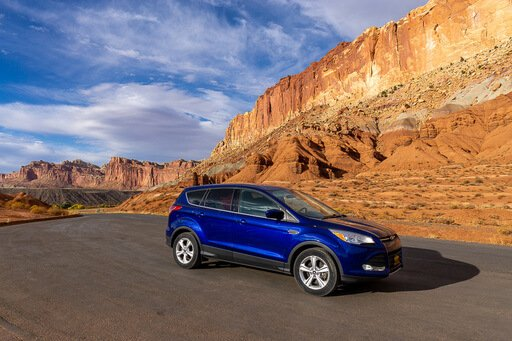 Front side view of our car at Capitol Reef with red rocks behind