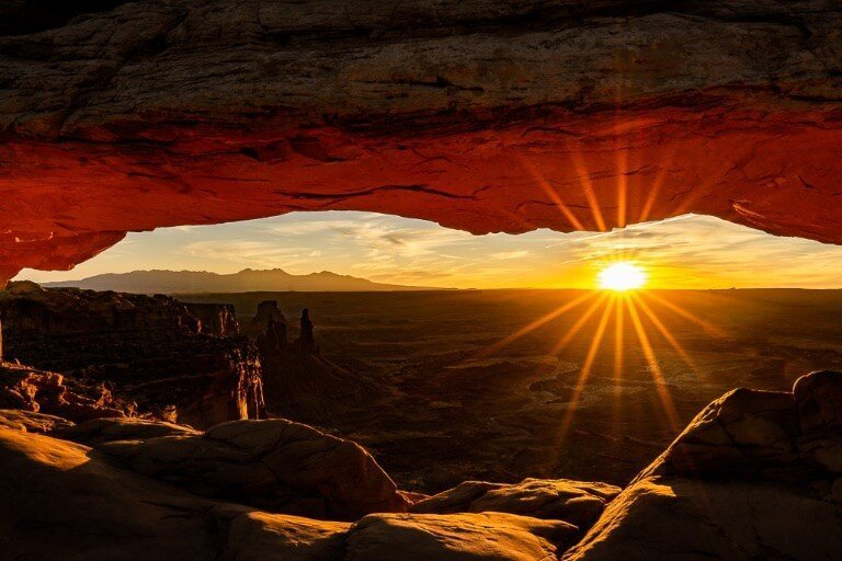 Bright sunburst illuminating mesa arch at sunrise Canyonlands national park Utah