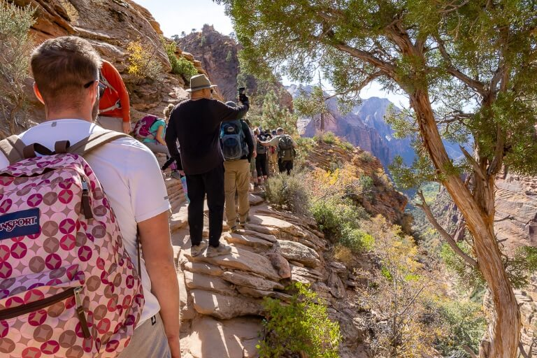 Mark at Angels landing narrow ledge and path with many other people on the trail