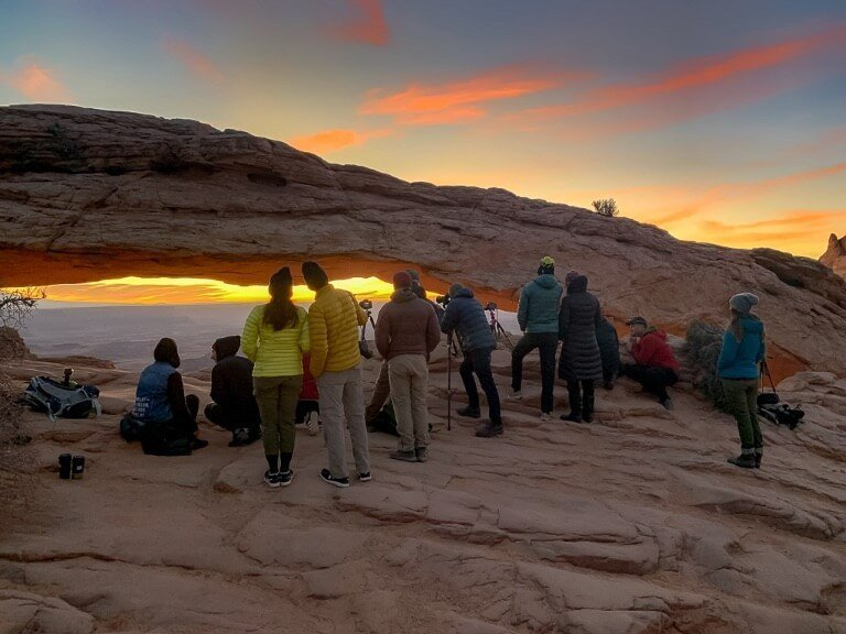 Small crowd of photographers in a line at Mesa Arch Canyonlands watching sunrise over the canyon