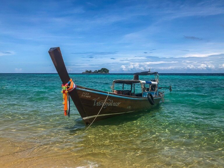 Long tail boat on clear turquoise water on Koh Lipe Itinerary Thailand