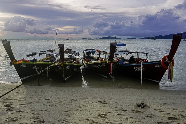 4 long tail boats lined up along sunset beach Thailand