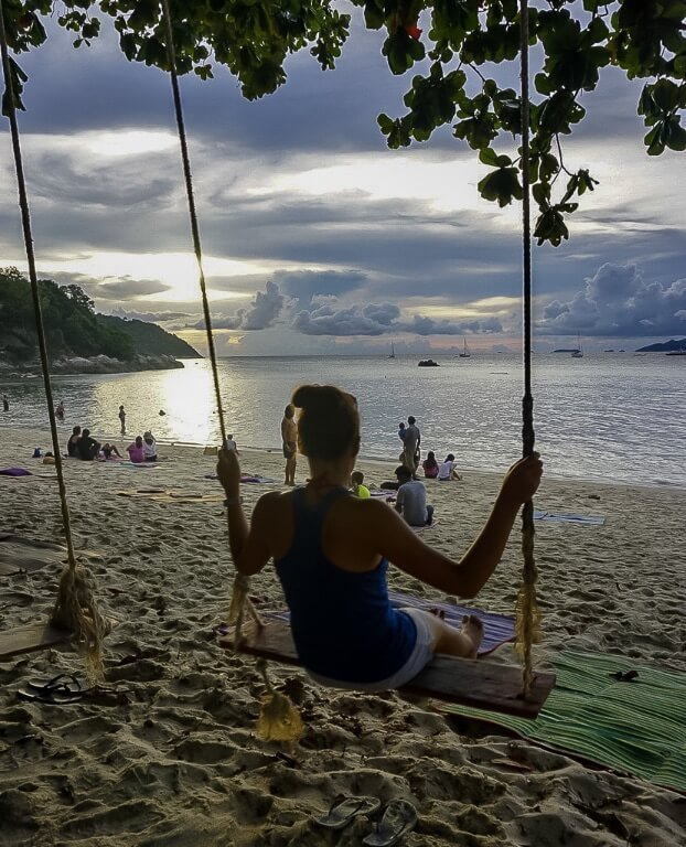 Kristen on a wooden rope swing at Sunset beach Koh Lipe with awesome clouds illuminated
