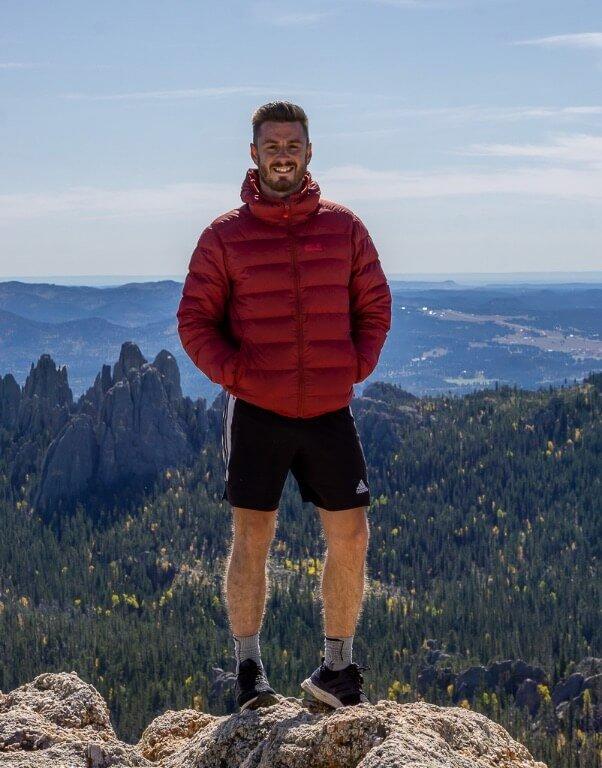Mark at summit of Black Elk Peak hike wearing thick grey hiking socks tips for beginners