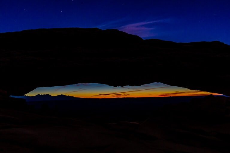 Mesa Arch before twilight deep purples and silhouetted rock formation