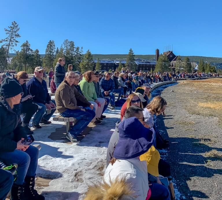 Old Faithful bleachers crowds of tourists watching famous eruption