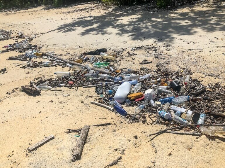 Loads of trash along a narrow beach on a secluded Thai island