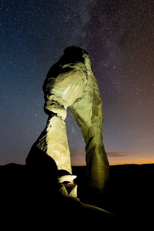 Delicate Arch astrophotography painted the arch with torch amazing colors one day in arches and canyonlands national parks Utah road trip