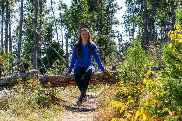 Kristen sat on a log in South Dakota Black Hills National Forest