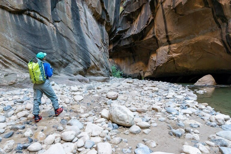 Kristen standing on rocky path next to river in slot canyon the Narrows hiking trail Zion national park