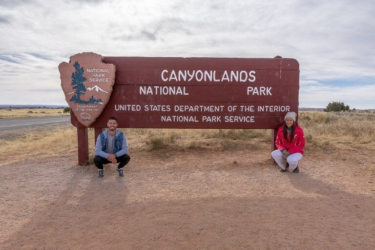 Mark and Kristen Where Are Those Morgans kneeling in front of canyonlands national park entrance sign