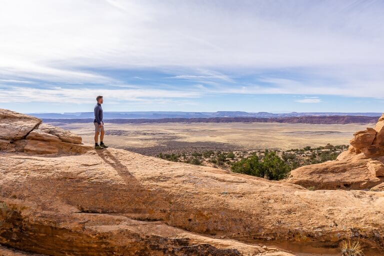 Mark on huge orange rock with amazing valley view in background arches national park Utah