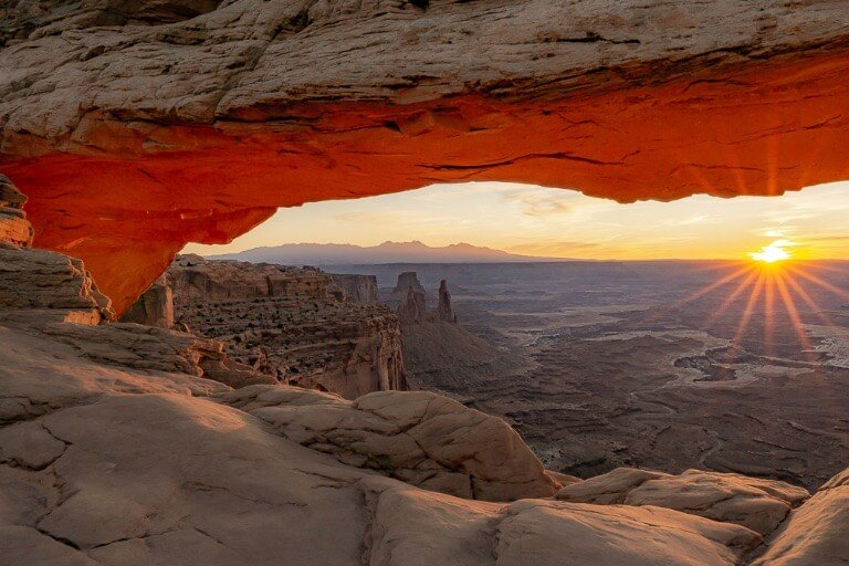 Sunrise with sunburst over canyonlands national park mesa arch one day in arches and Canyonlands national parks Utah