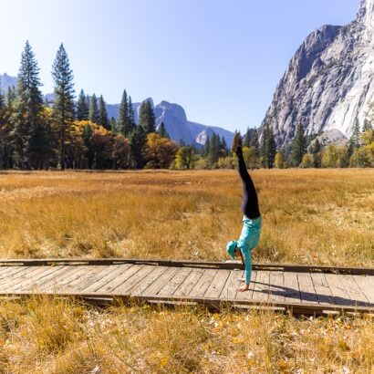 Kristen crushing a handstand on a boardwalk at Yosemite national park valley in fall