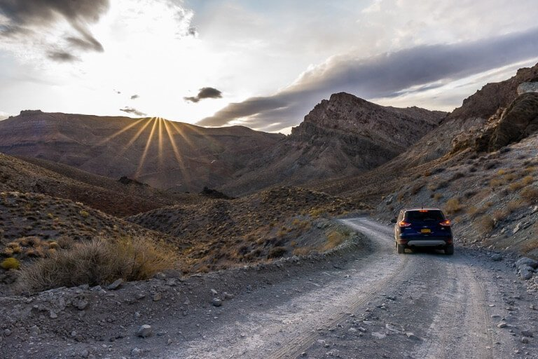 Our car on titus canyon road with sun star incredible scenery Death Valley national park California