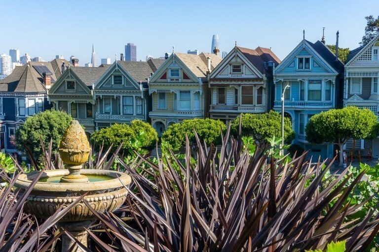 Painted ladies famous houses from full house tv show in San Francisco from behind plants and birdbath