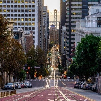 San Francisco tram lanes and Oakland bridge early just after sunrise