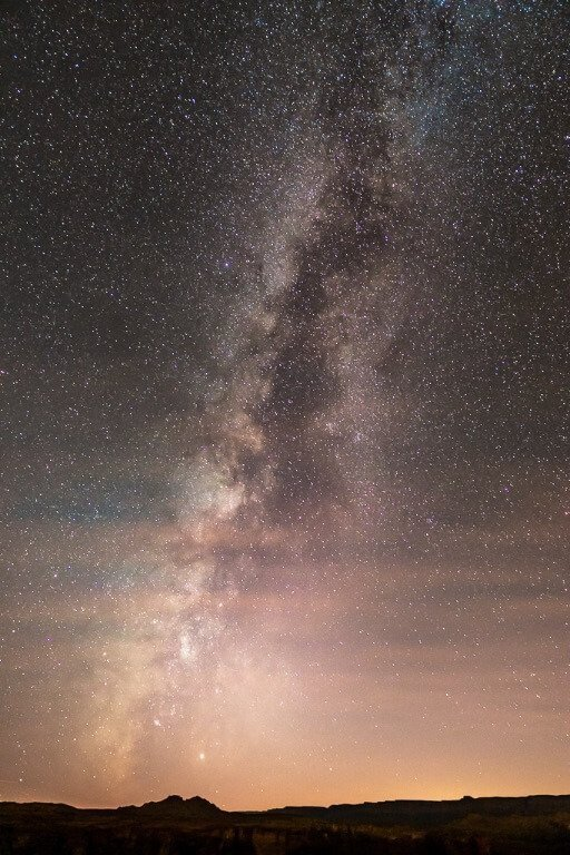 Milky Way bursting out of clouds and sunset