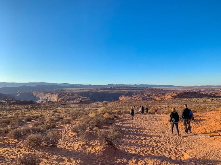 Walking along sandy trail from parking lot to Horseshoe Bend overlook in late afternoon with clear blue sky