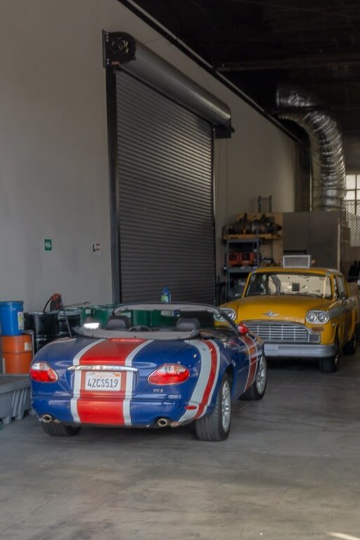 Austin powers car and phoebe's taxi from friends in garage on movie studio lot