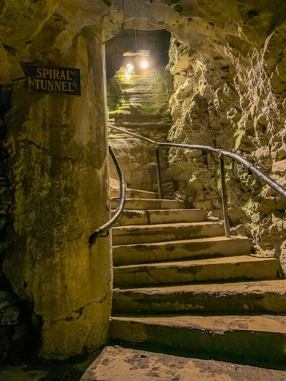 Spiral stone staircase illuminated by bright lights