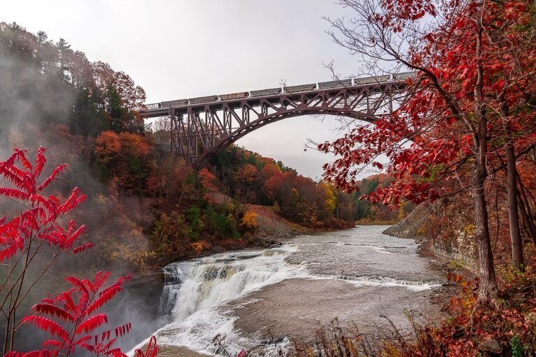 Stunning fall colors around letchworth state park upper falls with train crossing steel arches railroad bridge for a fantastic image