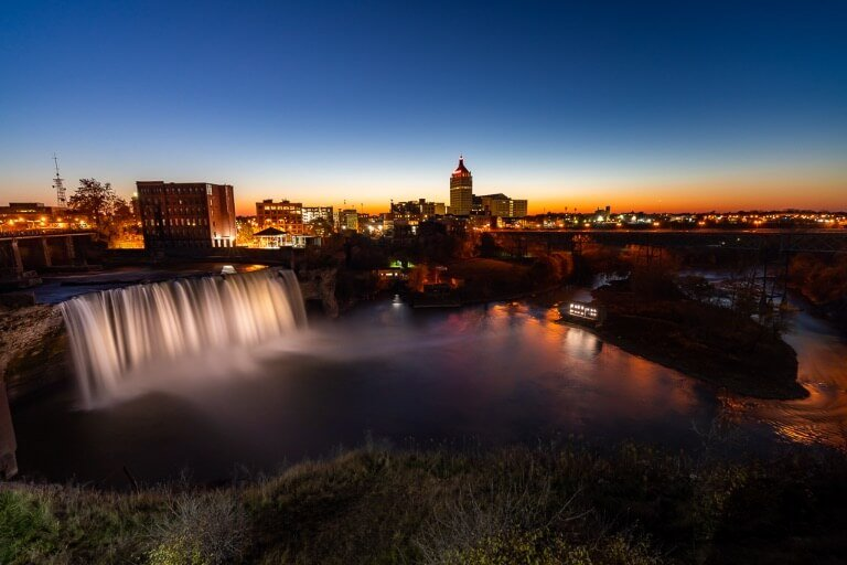 Rochester High Falls in the center of the city awesome waterfalls in New York Finger Lakes especially at night with the waterfall lit up and the kodak building in the background center