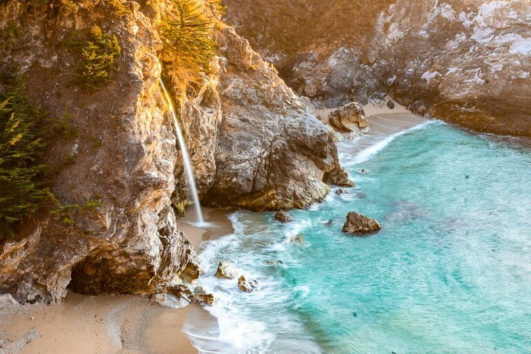 McWay falls is the single most stunning natural feature along California Pacific coast highway 1 thin waterfall plunging onto a sandy beach and joining the ocean as the tide gently washes in