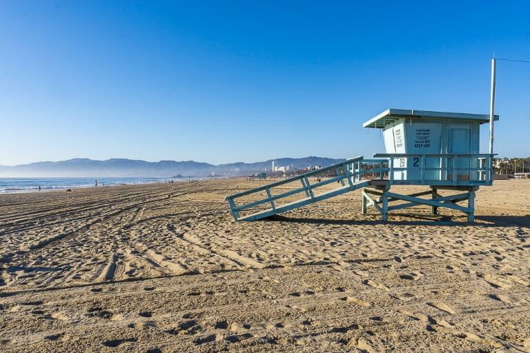 Walk to Venice Beach from Santa Monica past lifeguard cabins along the sand