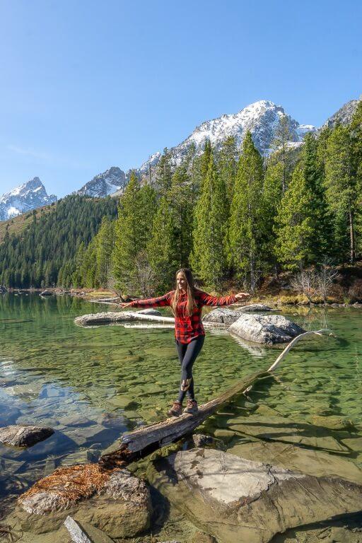 Kristen walking across a log in a lake in Wyoming