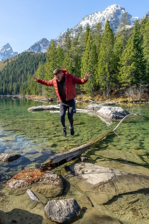 Mark jumping on a log in a clear lake in Wyoming